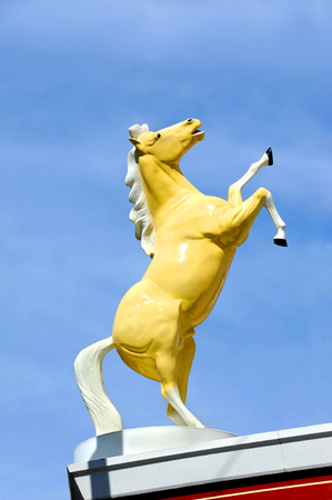 rearing: Statue of a wild stallion rearing its legs into the air, is sillouetted against a blue sky in Montana.  Wild west symbol. Stock Photo