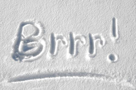 message: Handwritten message in the snow says Brrr.