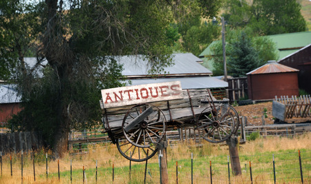 antiques: Dilapidated and weathered, wooden wagon hangs as part of an antique sign advertising antiques for sale.  Sign hangs in Montana.
