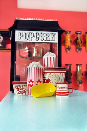Home movies are so much better with fresh popcorn!  Popcorn sits in holders and yellow scoop sits ready for seconds.