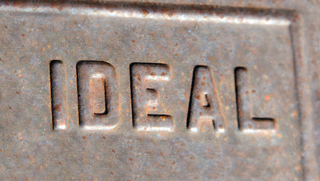 standard steel: Letters spelling Ideal, are weathered and old.  Raised metal letters are faded and rusted.