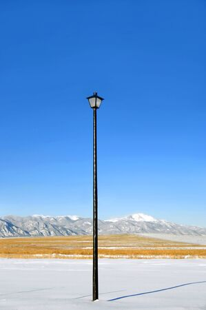 fronts: Extremely tall street light serves as night security in Colorado Springs.  Lamp tops black, iron pole.  Pole fronts Pikes Peak and the Rocky Mountains.