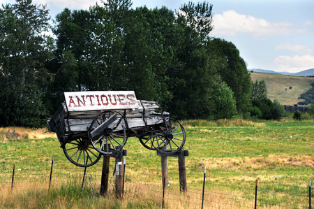 old wood farm wagon: Weathered and rotting, wooden wagon sits atop a metal fence.  Wagon has a cracked and peeling sign attached with the word antiques on it.