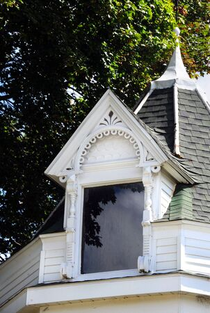 dormer: Beautiful window dormer is wooden and painted white.  Architecture is intricate and beautiful.