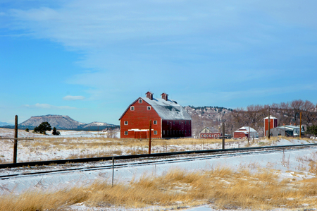 wood railroad: Snow lays around railroad tracks and sits on barn roof.  Barn is a two story, red, wooden building.