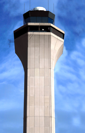 control tower: Denver airport, control tower is framed by blue sky.