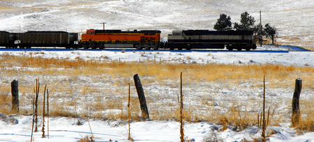 fronts: Coal train hauls coal across the plains fronting the Colorado Rocky Mountains.  Fence fronts train.