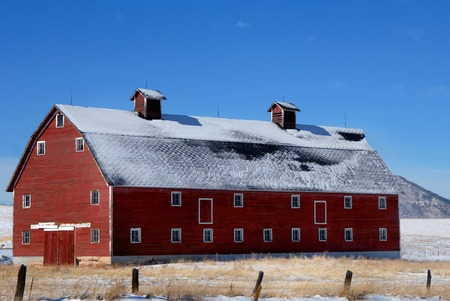 three story: Old, red, wooden barn sits on a field in Colorado.  It is three story with dormers on top.  Light layer of snow covers field and roof.