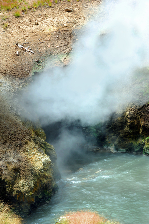 hydrothermal: Steam and vapors escape landmark known as Dragons Mouth Spring in Yellowstone National Park.  Water boils at entrance to dragons mouth.