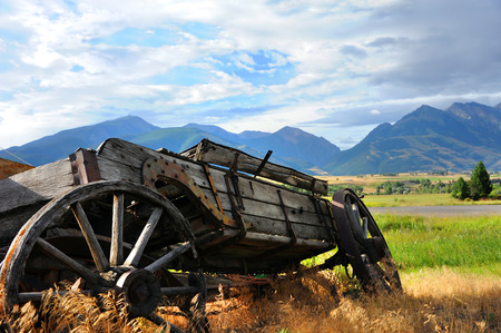 carreta madera: Broken down, wooden wagon sits overgrown with weeds.  It has a view of distant Absaroka Mountains in Paradise Valley, Wyoming. Foto de archivo