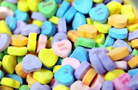Pile of heart shaped candy sits ready for sale.  Message on one heart says say yes. Stock Photo