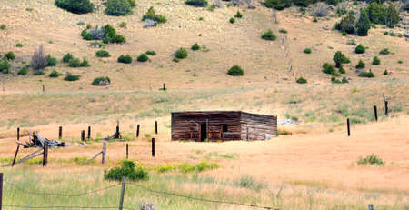 Roofless log cabin is surrounded by old rustic fence.  Cabin sits in Happy Valley, Wyoming. Stock Photo
