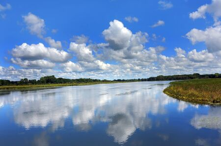 The view from the Yahara River Trail, is smooth as glass.  Reflection of sky and clouds turn water into blue.