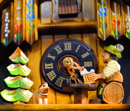 reloj cucu: Cuckoo clock shows man sitting on a log drinking a bear while his dog keeps him company.  Swiss chalet and clock piece in background. Foto de archivo