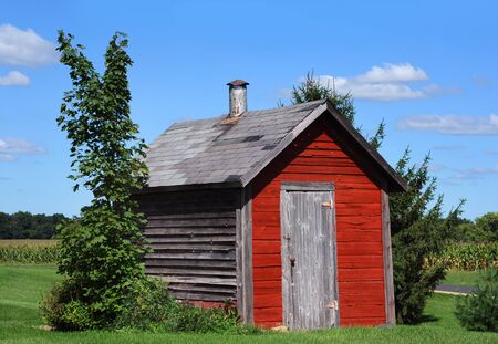 stove pipe: Red, wooden, smokehouse sits on farm in Wisconsin.  Smoke pipe peaks out of the roof.  Wood is weathered and old. Stock Photo