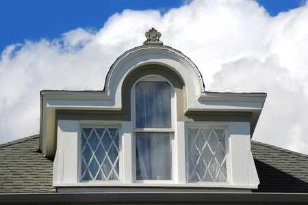 dormer: Three glass windows set inside arched dormer on elegant Victorian home in Stoughton, Wisconsin. Editorial