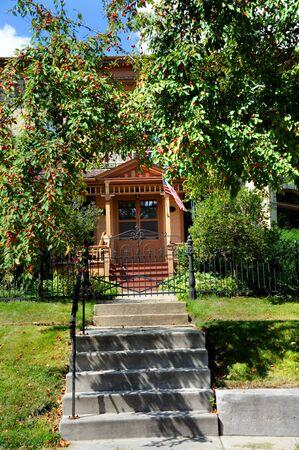 Kirschbaum Auskragungen Eingang zum gemütlichen viktorianischen Haus in Wisconsin. Eisentor, fliegende amerikanische Flagge und Veranda zu behaglicher Atmosphäre hinzuzufügen.