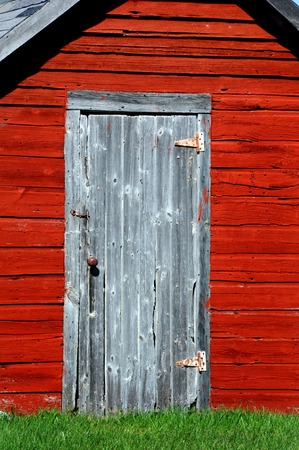 stove pipe: Rustic, wooden door sits on front of an old red smokehouse in rural Wisconsin.  Hook holds door closed. Stock Photo