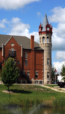 victorian architecture: Side view of the Stoughton, Wisconsin, Opera House and City Hall.  Round tower houses four clocks in dormers with Victorian architecture.