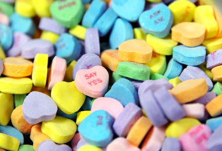 Pile of heart shaped candy sits ready for sale.  Message on one heart says say yes and one at the back answers just ask me. Stock Photo