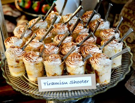Wedding reception offers guests a Tiramisu Shooter.  Plate holds group of desert glasses with spoons. Imagens