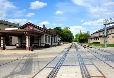 them: Image taken from center of tracks shows them disappearing into the distance.  Old historic train depot sits besides tracks in Stoughton, Wisconsin. Stock Photo