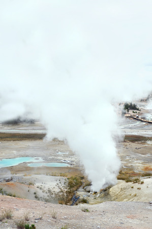 Steam spews from geyser in Norris Geyser Basin in Yellowstone National Park.  Palette Springs can be seen in background.