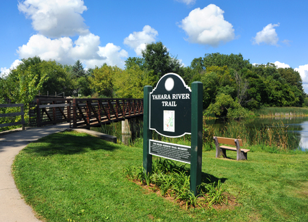 Beginning of the Yahara River Trail, in Stoughton, Wisconsin, has bridge over river. Sign stands in front of a park bench by the water.