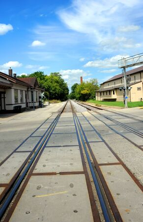 mid distance: Historic train depot sits besides railroad tracks in Stoughton, Wisconsin.  Tracks disappear into distance. Stock Photo