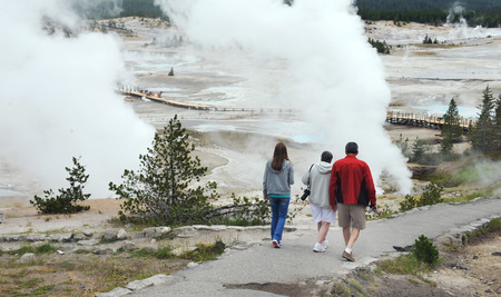 geysers: Family visits Norris Geyser Basin in Yellowstone National Park.  They carry cameras and a hiking down to geysers via walkway. Editorial