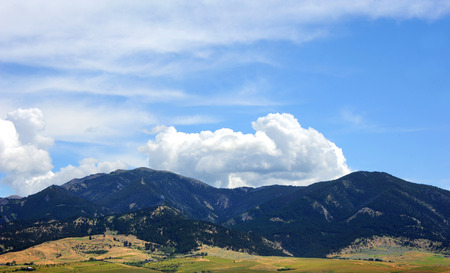 bridger: Bridger Mountain Range, near Bozeman, Montana, is covered in trees and fluffy clouds.