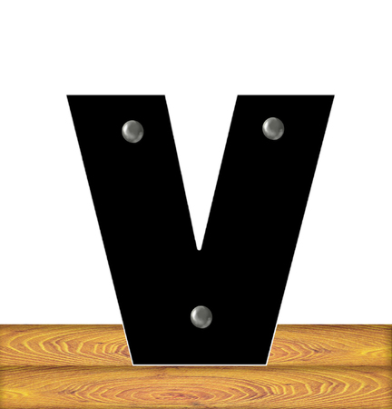 The letter V, in the alphabet set Construction, is black with silver nails embedded in letter.  Letter sits on wooden planks.