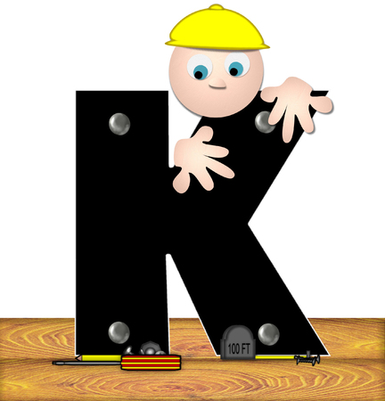 inspecting: The letter K, in the alphabet set Construction Worker, is black with silver nails embedded in letter.  Construction worker bends over inspecting letter.  Tools sit beside letter on wooden planks. Stock Photo