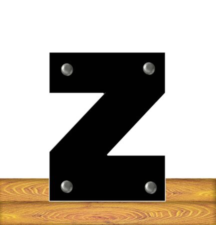 The letter Z, in the alphabet set Construction, is black with silver nails embedded in letter.  Letter sits on wooden planks. Stock fotó