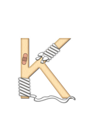 doctoring: Alphabet letter K, in the set Boo Boo, is tan to represent the color of skin.  Each letter is bandaged and has bandaids applied.  Strips of guaze and scissors also decorate letters. Stock Photo