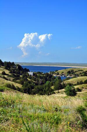 nebraska: Hills of Nebraska grassland hide a beautiful Lake called McConaughy.  Blue sky is reflected in blue water.