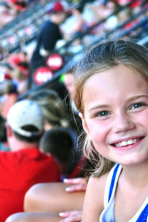 Little girl smiles her excitement as she sits at her first professional baseball game.  She sits in the stands with her family.
