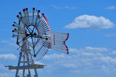 nebraska: Unusual wildmill is metal with red tipped blades.  Blue sky and clouds frame windmill.