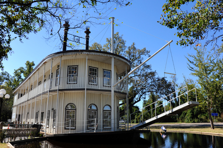 Double decker, paddle boat serves as a visitors center for Greenville, Mississippi.  Boat is white with black trim and floats on water.