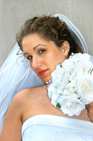 solemn: Beautiful young bride holds her bouquet close to her face.  She is solemn and glancing over her flowers at the camera. Stock Photo