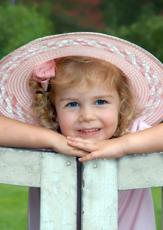 Beautiful little girl, wearing a pink hat and dress, rests her chin on her hands and smiles.  She is leaning on a rustic, white wooden gate.