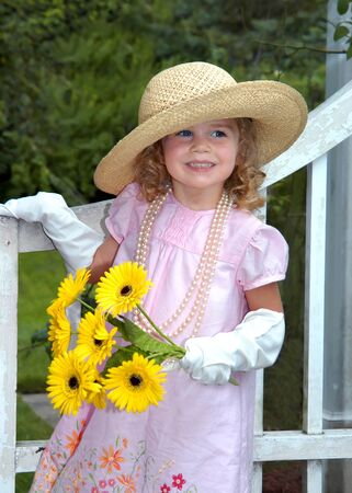 Beautiful little girl plays dressup in the park.  She is wearing white gloves, pearls and a straw hat.  She is holding some flowers. photo