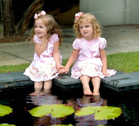 Two beautiful little girls sit side-by-side on the edge of a lilly pad pond.  They are wetting their feet and laughing and smiling.  Dresses are pink. photo