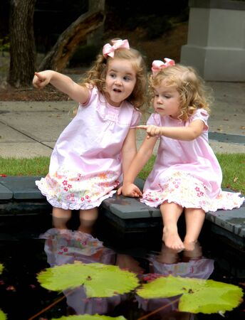 Two beautiful girls sit side by side on a lilly pad pool.  They are pointing in different directions and having different opinions.  They are wearing pink dresses. photo