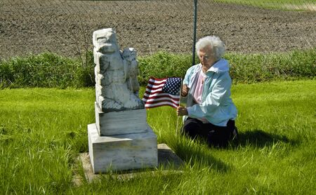 Mother places an American flag at the tomb of her loved one.  She is kneeling besides the grave on the grass. Stock Photo