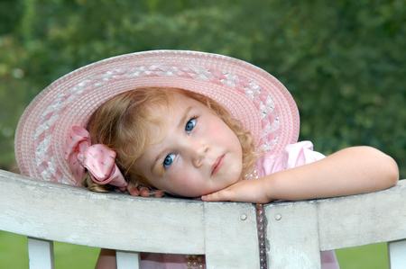 Adorable in a pink hat, little girl leans her head against a rustic wooden gate.  She  has an angelic expression of pur innocence.