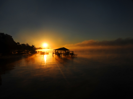 Lake Chicot is bathed in golden sunrise.  Pier and boat house are silhouetted against the early morning golden sunrays.