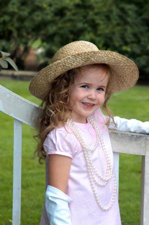 Mooi meisje, gekleed in een roze hoed en kleding, rust een gehandschoende hand op een rustieke houten hek. Ze is ook het dragen van een lange strand van peren. Stockfoto