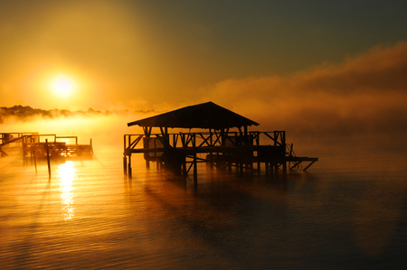 boat house: Early morning mist rises from Lake Chicot in Lake Village, Arkansas.  Wooden dock and boat house are silhouetted. Golden light covers lake.