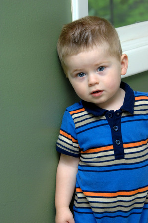 Adorable little boy stands against the wall of his home.  He has on a striped one piece and has his mouth slightly open. photo